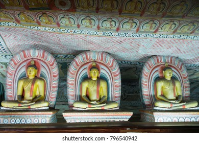 Group of sitting Buddha statues in cave buddhist temple with bright painted murals on walls and ceiling