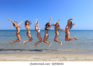 Group of Six Attractive girl jumping on the beach in Greece