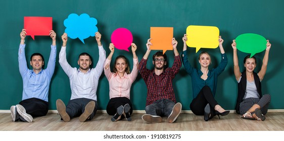 Group of six business people team sittiing together and holding colorful and different shapes of speech bubbles