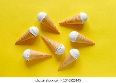 Group of six cones with creamy vanilla ice cream or gelato on a vivid yellow background arranged in the centre