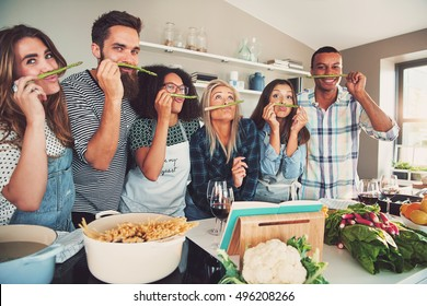 Group of six diverse silly adults sniffing asparagus stalks in kitchen. Bowl of pasta and vegetables are on the table.