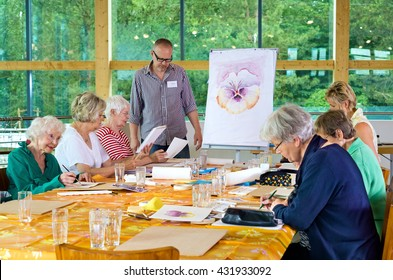 Group of six female senior citizens at long table in painting class with male teacher in glasses standing near front