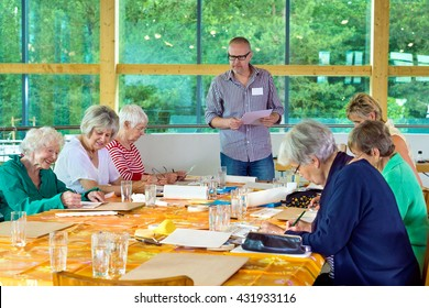 Group of six female senior citizens at long table in art class with male teacher in glasses standing near front beside large windows facing green trees