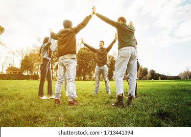 Group of six friends at the park at sunset holding hands in the air - Teamwork - Concept of unity and collaboration