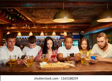 Group of six friends with serious facial expression, sitting with smartphones, drinking beer at bar. Young people addicted to gadgets, looking at mobile screens. Everyone with own smartphone.