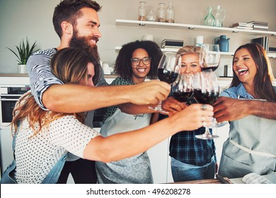 Group of six good friends toasting with wine glasses in cozy kitchen during a dinner party