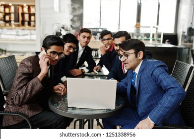 Group of six indian business man in suits sitting at office on cafe and looking at laptop.