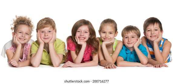 Group of six joyful children are lying on the floor on a white background