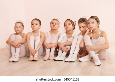 A group of six little ballerinas sitting on the floor gathered around their teacher and listen to advice. They are good friend and amazing dance performers