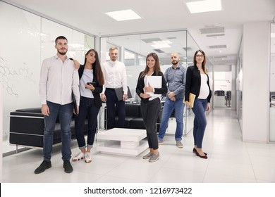 "group of six people posing, looking at camera, 20-29 years and 30-39 years old, of various white-collar workers, dressed ""smart casual"". modern office interior hallway."