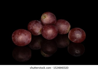 Group of six whole fresh purple grape rose isolated on black glass