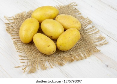 Group of six whole pale yellow potato on natural sackcloth on white wood