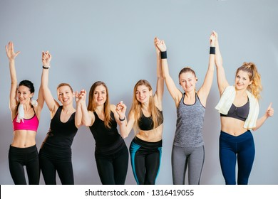 Group of six young sporty girls holding by hands while standing at grey wall in pilates studio. Female companions in gym resting after fitness, indoor.