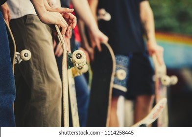 Group of skaters with skateboards standing on ramp top ready to do tricks on street contest.Fun summer extreme sport for young and active people.Healthy teenager lifestyle