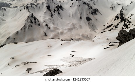 A group of ski touring enthusiasts moving trough an avalanche terrain with high avalanche risk level