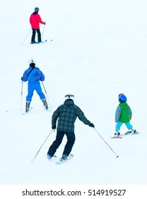Group of a skiers on a mountain slope at ski resort. Back view