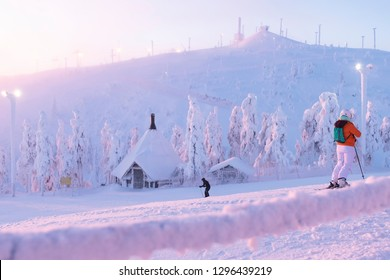 A group of skiers slide from the top of the mountain in the sun. Early morning. sunrise. Kuusamo Ruka. Finland. Panorama view. - Shutterstock ID 1296439219