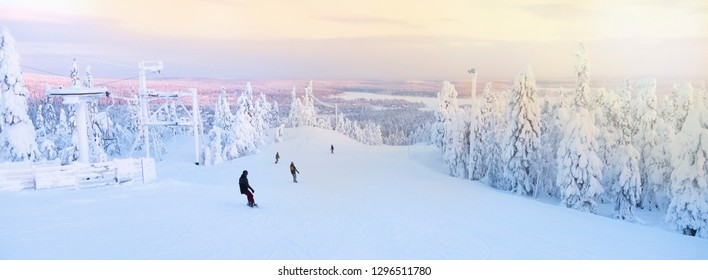 Group, skiers and snowboarders slide down the mountain.  Sunrise over the snow-covered forest. Kuusamo Ruka. Finland. Panorama view. - Shutterstock ID 1296511780