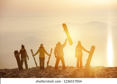 Group of skiers and snowboarders at sunset. Ski resort concept