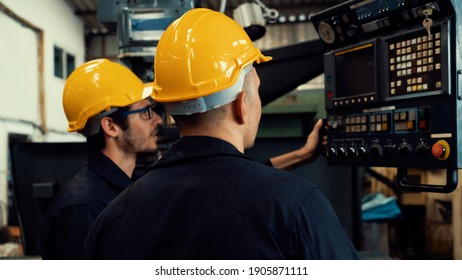 Group of skillful factory workers using machine equipment in workshop . Industry and engineering people technology concept .