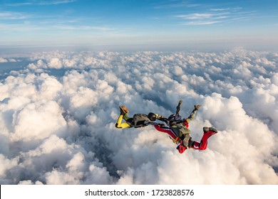 Group of skydivers above the clouds.