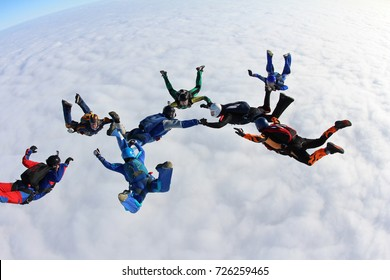 The group of skydivers above white clouds.