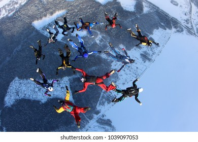A group of skydivers is in the winter sky.