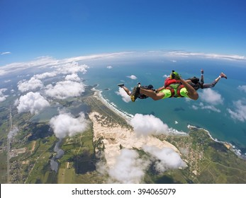 A group of skydiving friends having fun in the skies. Soft focus in background. Ibiraquera Brazil.