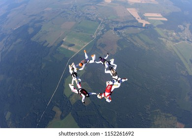 Group skydiving. Letter O in the sky.