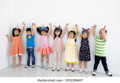 Group of small asian children have birthday party, wearing festive hat , they feel happy to play together