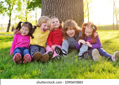 a group of small children in colorful clothes embracing sitting on the grass under a tree in a park laughing and smiling. June 1, Children's Day, vacation, friendship, friends, childhood.