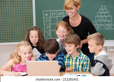 Group of small children ion class with a teacher clustered around a laptop computer laughing and smiling as an attractive woman keeps an eye on them