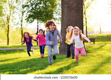 a group of small happy children run through the park in the background of grass and trees. Children's outdoor games, vacations, weekend, Children's Day, June 1