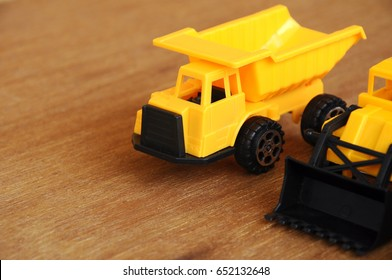 Group of small heavy construction machine toy, lorry, bulldozer and concrete mixer. All made of plastic isolated on a wood grain texture background.