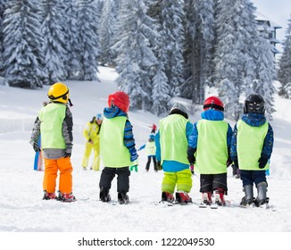 Group of small kids with helmets and vests standing on skis and learning basic skills for skiing at polygon