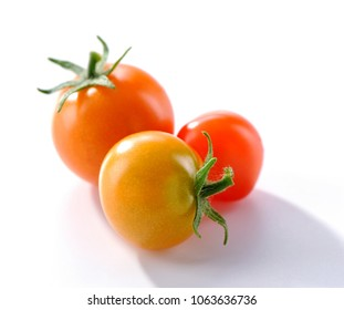 group of small red and yellow tomatoes close-up on white background