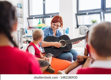A group of small school kids and teacher with guitar sitting on the floor in class.
