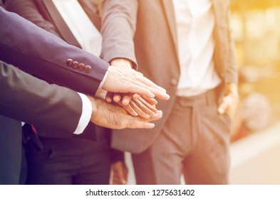 Group of smart business men and women put hands together as a symbol of business coorporation, in soft light tone