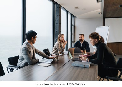 Group of smart motivated businesspeople working together on a new project while sitting at the table in the office