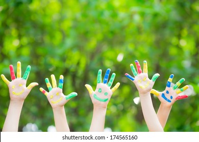 Group of smiley hands against green spring background