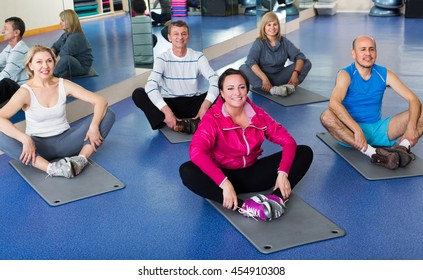 Group of smiling active adults doing pilates routine in a sport club