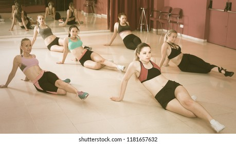 Group of smiling active females training zumba movements in dance class