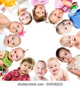 Group of smiling babies standing in huddle on white