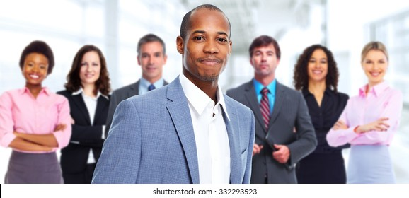 Group of smiling business people over office background.
