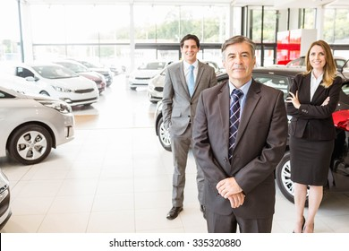 Group of smiling business team standing together at new car showroom