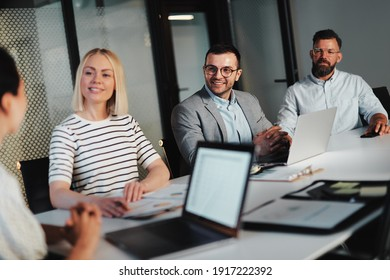 Group of smiling businesspeople talking together during a meeting around a table in the boardroom of a modern office