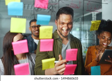Group of smiling casual business people planning and writing project and ideas over the sticky notes pasted on glass wall at modern office