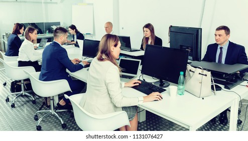 Group of smiling cheerful successful business people during daily work in modern co-working space