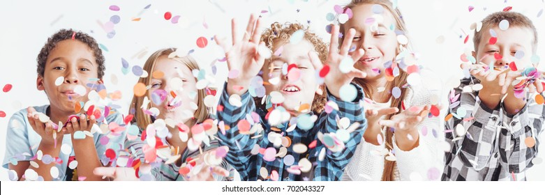 Group of smiling children in casual clothes throwing confetti around them