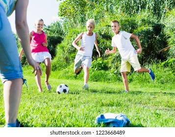 Group of smiling children having fun together outdoors playing football